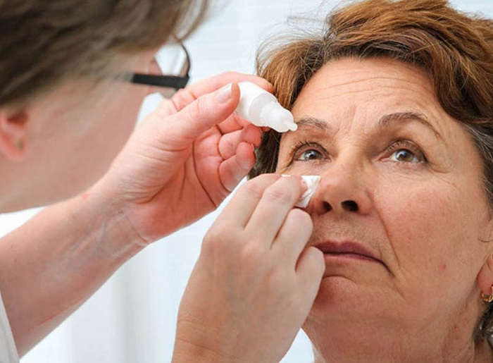 Доктор закапывает женщине глаза