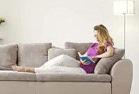 Девушка читает на диване