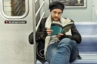 Мужчина читает в транспорте