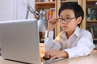 Мальчик в очках за ноутбуком