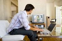 Мужчина смотрит телевизор и сидит за ноутбуком