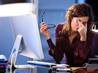 Девушка трет глаза за компьютером