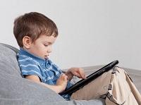 Ребенок сидит за планшетом