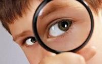 Ребенок с лупой возле глаза