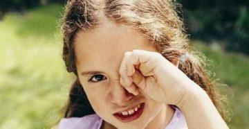 Девочка трет глаз рукой
